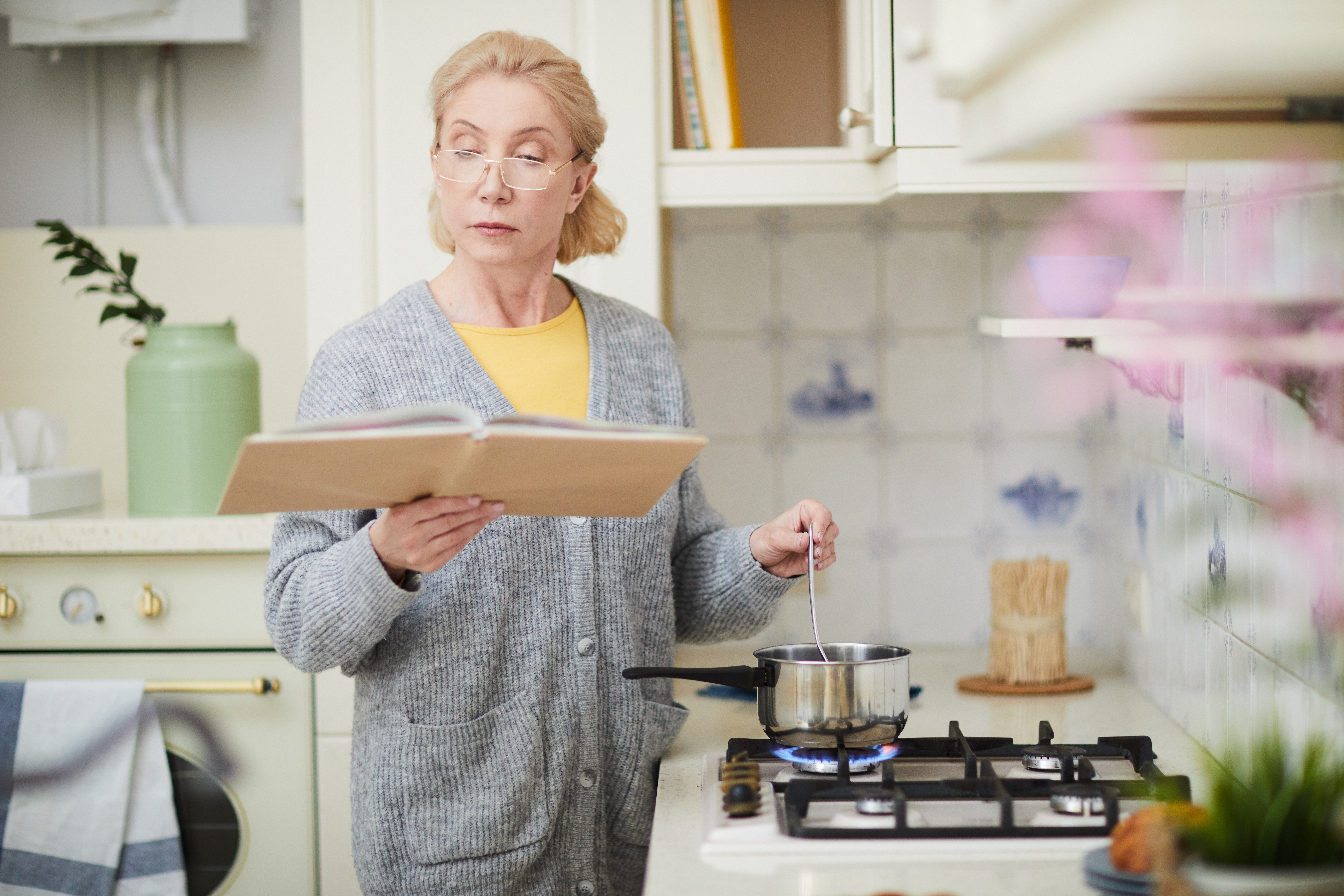 Woman Cooking In Kitchen With Recipe Card Binder